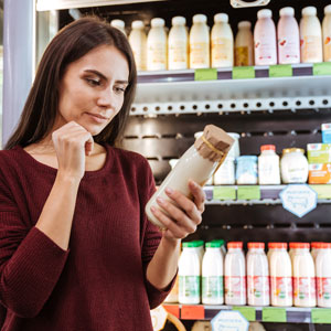 Pensive young woman choosing yogurt in grocery shop